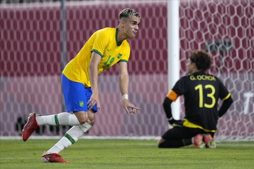 Brazil soccer player Reinier celebrates after scoring the winning goal as Mexico's Guillermo Ochoa kneels.
