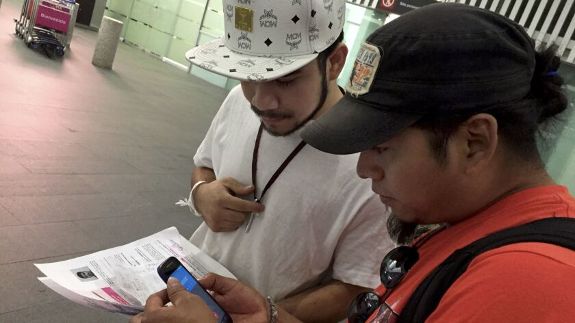 Roger Perez, left, receives help from Diego Maria, who is a part of a group called Deportees United in the Fight. The group, made up of former deportees, goes to the airport each week to greet those who, like them, have been forced to return.