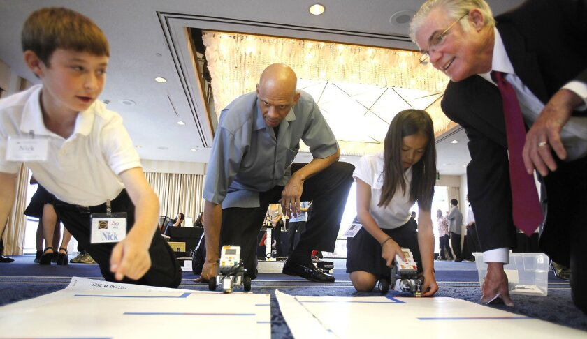Avivara Oaks Middle School students Nick Conklin (left) and Katrina Dang show Kareem Abdul-Jabbar and state schools chief Tom Torlakson their robot project during a STEM summit at the Sheraton Harbor Island in October 2012.