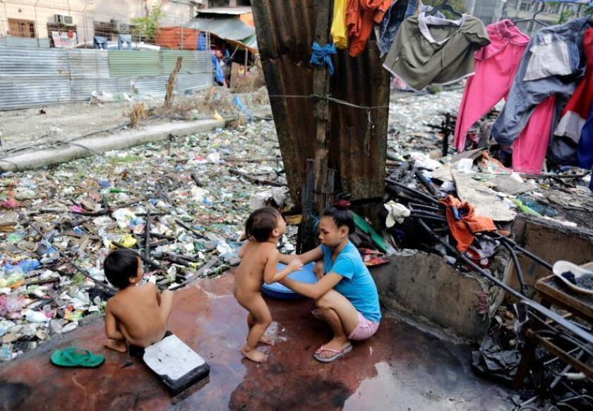 Varios niños se duchan junto a un canal repleto de basura en Manila (FIlipinas). EFE/Archivo