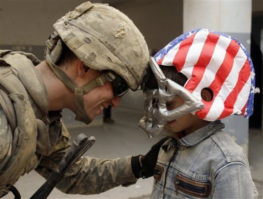 In this Nov. 5, 2008 file photo U.S. Army Sgt. Kyle Whalen, 22, from Plover, Wis., playfully taps his helmet with an Iraqi boy's donated toy football helmet during a visit to the boy's school in Mosul, 360 kilometers (225 miles) northwest of Baghdad, Iraq. When 21st-century Americans contemplate