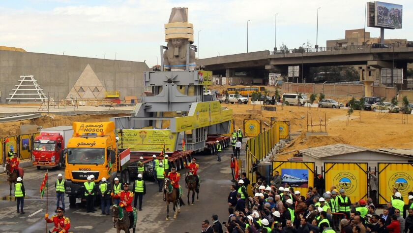 Egyptians celebrate as the giant granite statue of the ancient Pharaoh Ramses II is loaded onto a truck and transferred to its permanent home at the atrium of the Grand Egyptian Museum near Giza, Egypt.