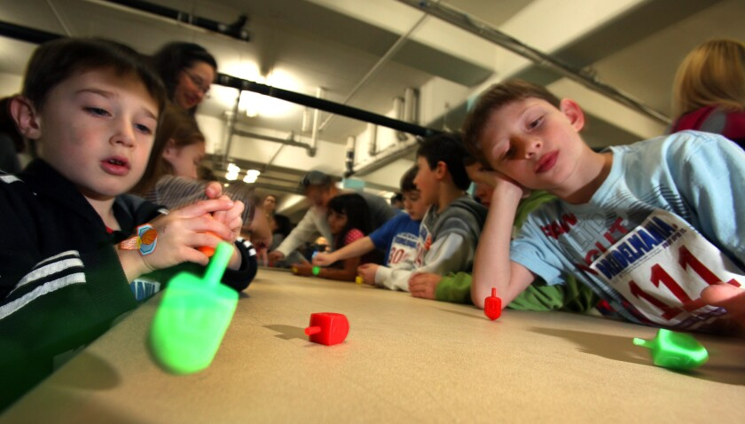 Children spin dreidels at Temple Sinai in Los Angeles.