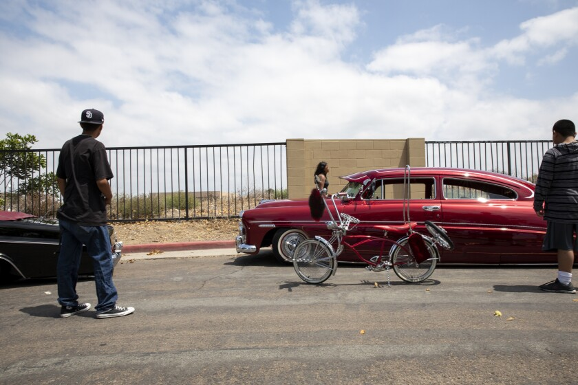 From left, Isaac Rosales, 16, moves his lowrider bicycle next to a 1949 Hudson Brougham.