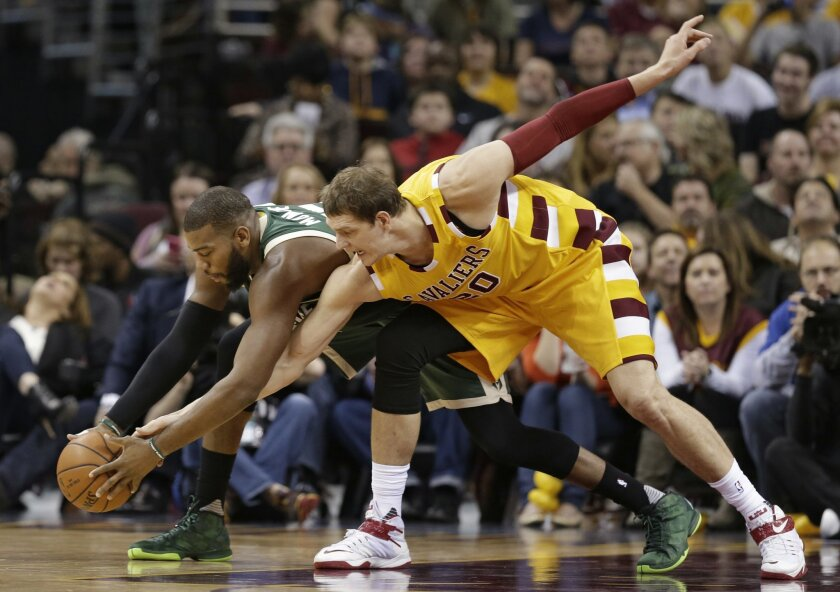 Milwaukee Bucks' Greg Monroe, left, and Cleveland Cavaliers' Timofey Mozgov (20), from Russia, battle for the ball in the first half of an NBA basketball game Thursday, Nov. 19, 2015, in Cleveland. The Cavaliers won 115-100. (AP Photo/Tony Dejak)