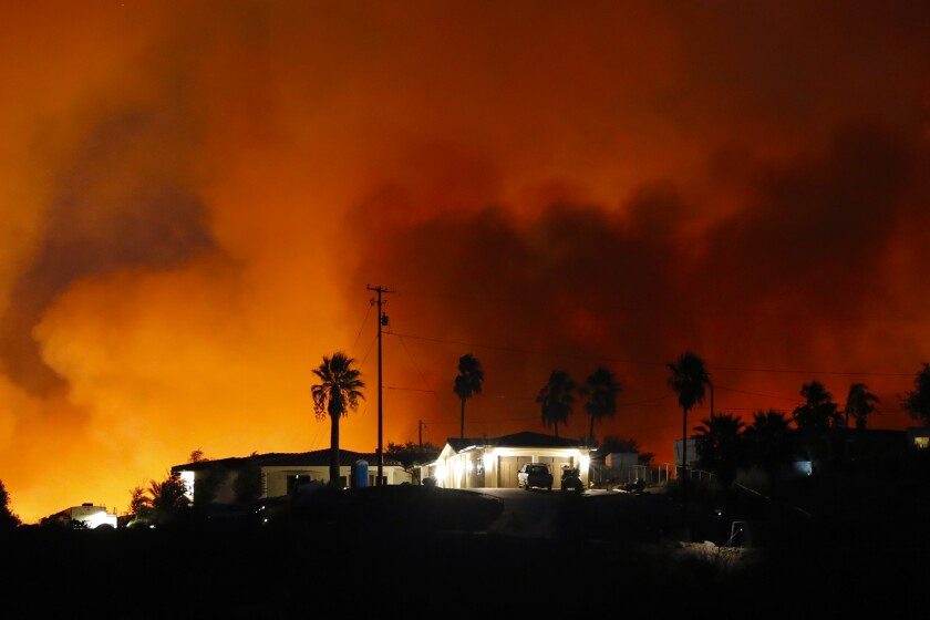 A home in Alpine, CA is surrounded by flames and smoke in the Valley Fire.