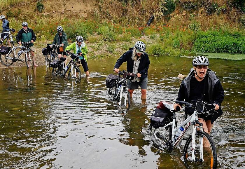 Knee-deep water in a usually dry riverbed in Catalonia didn't deter the resilient bikers, who waded through.