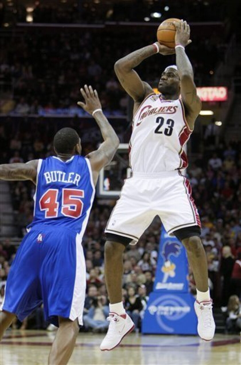 Cleveland Cavaliers' LeBron James (23) shoots a 3-point shot against Los Angeles Clippers' Rasual Butler (45) in the first quarter of an NBA basketball game Sunday, Jan. 31, 2010, in Cleveland. James tied a franchise record with five 3-pointers in a quarter. He made his first seven shots, including four 3s, to finish the quarter with 23 points. He had deep 3-pointers from 30 and 28 feet. (AP Photo/Mark Duncan)