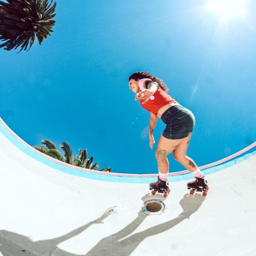 Picture of a woman roller skating on a rink with blue sky above.