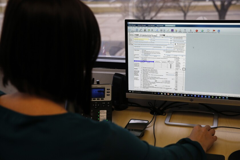In this Jan. 14, 2017, photo, tax professional and tax preparation firm owner Alicia Utley views a Form 1040 on her computer in her office at Infinite Tax Solutions, in Boulder, Colo. Millions of Americans are eligible for Earned Income Tax Credit but many overlook its generous benefits. A tax preparer and most major tax software can walk you through a series of questions to determine your eligibility.