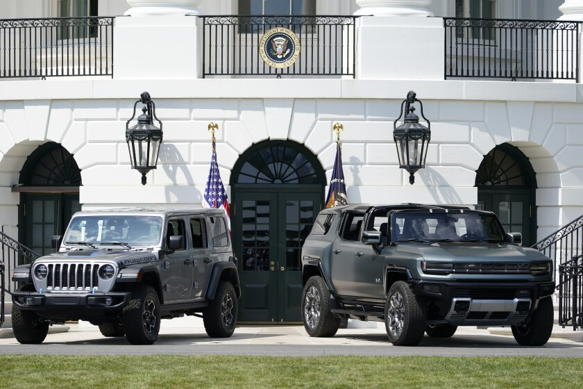 Two cars are shown on a driveway with flags behind them.