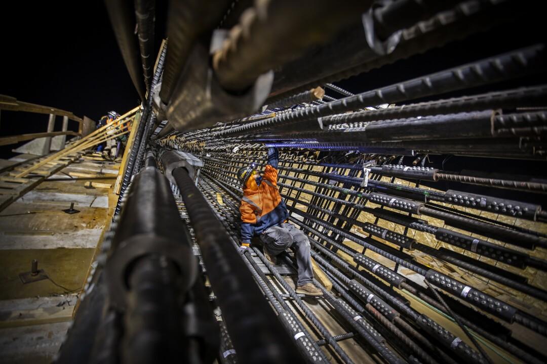 A construction worker climbs down an arch framework of reinforcing rods