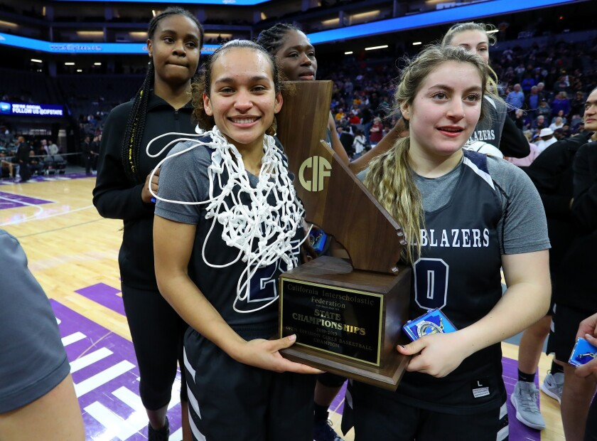 Sierra Canyon's Ashley Chevalier, left, with a cut basketball net around her neck and a teammate hold last season's state championship trophy.