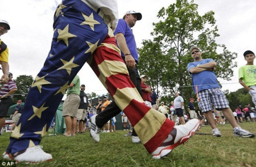 John Daly, front with patriotic pants, walks with fellow golfer, Peter Hanson, right, during the first round of the Greenbrier Classic PGA tour golf tournament at the Greenbrier in White Sulphur Springs, W.Va.
