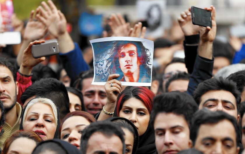 A fan holds up a photo of Iranian pop star Morteza Pashaei during his funeral in Tehran on Sunday. Pashaei died Friday after battling stomach cancer. He was 30.