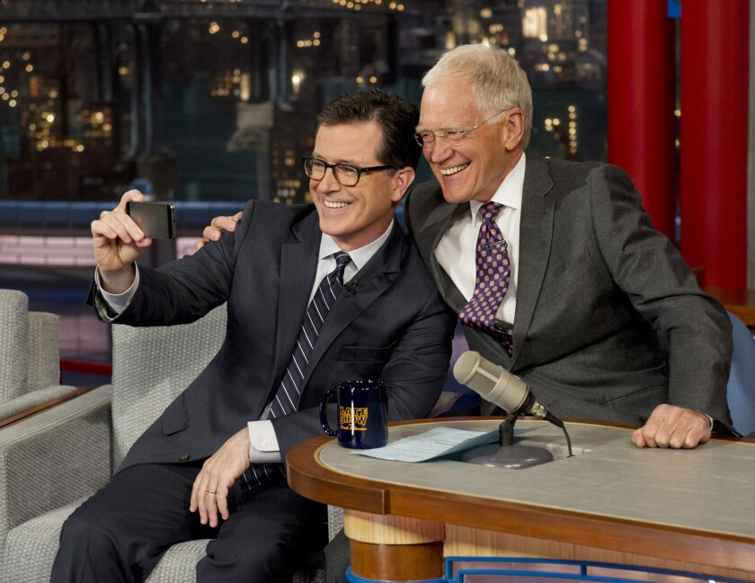 """David Letterman, right, smiles for a selfie with Comedy Central's Stephen Colbert on the set of """"Late Show with David Letterman"""" on April 22."""