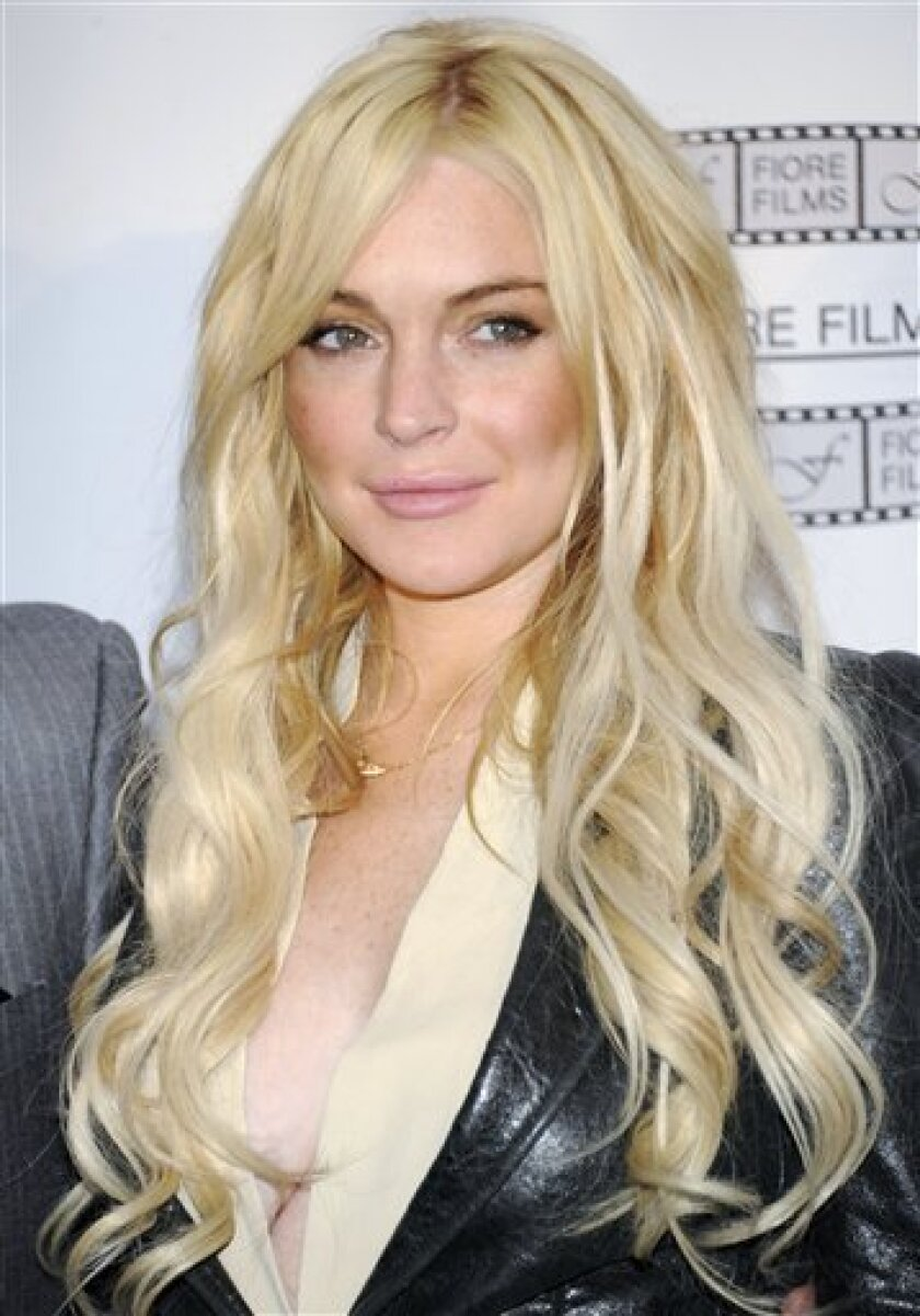 """FILE - In this April 12, 2011 file photo, actress Lindsay Lohan poses during a news conference for the film """"Gotti: Three Generations"""", based on the life of John Gotti, in New York. A source close to Lohan says the actress wants to end a misdemeanor theft case filed after a jewelry store reported the actress took a necklace without permission, according to a report Saturday April 30, 2011. (AP Photo/Evan Agostini, file)"""