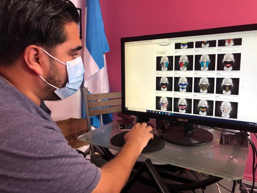Luis Villagrán muestra los diseños que están disponibles en la tienda que tiene su empresa 502 Graphics.
