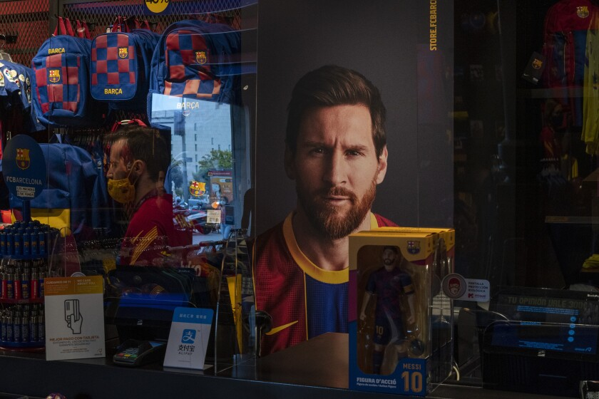 A poster with the face of Barcelona soccer player Lionel Messi is displayed at a F.C. Barcelona store in Barcelona, Spain on Tuesday, Sept. 1, 2020. Barcelona is banking on a face-to-face meeting with Lionel Messi to try to convince him to stay. Talks with Messi's father-agent are expected this week in Barcelona but the club also hopes to sit down with the player himself.(AP Photo/Emilio Morenatti)