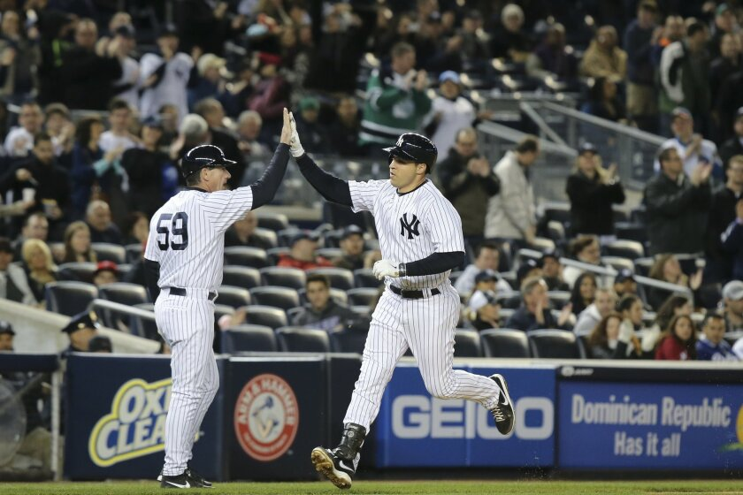 New York Yankees first baseman Mark Teixeira celebrates with third base coach Rob Thomson as he runs home from his solo home run in the seventh inning their baseball game against the Los Angeles Angels at Yankee Stadium, Sunday, April 27, 2014, in New York. (AP Photo/John Minchillo)