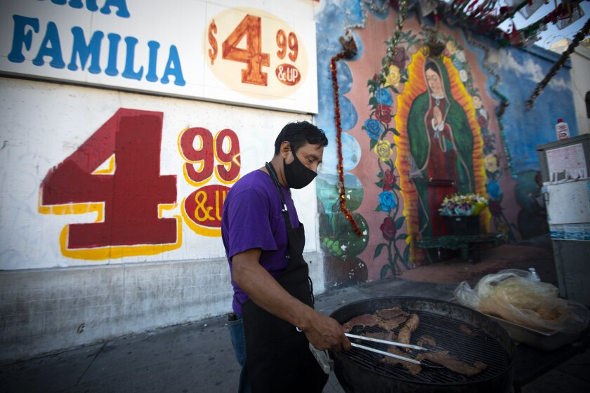 Clemente Gomez cooks carne asada on the grill outside a food truck in the Westlake neighborhood of Los Angeles.