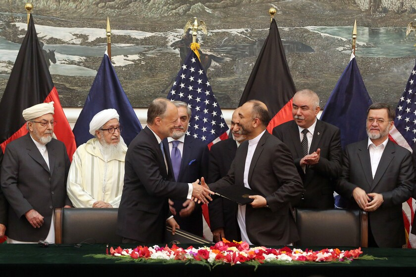 Afghanistan's national security advisor, Mohammad Hanif Atmar, third from right, and U.S. Ambassador James Cunningham shake hands Sept. 30 after signing a security agreement that will allow American troops to remain in Afghanistan.