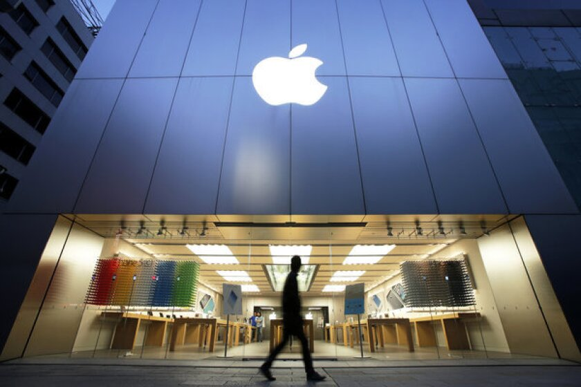 A man walks past an Apple store in Tokyo.