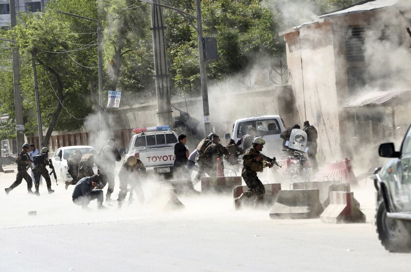 Security forces run from the site of a suicide attack Monday after the second bombing in Kabul, Afghanistan.