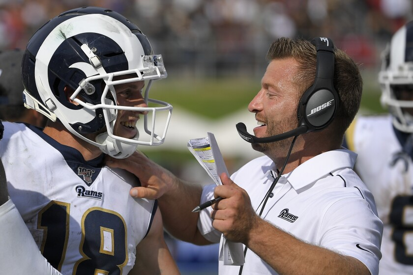 Rams wide receiver Cooper Kupp stiff-arms Saints cornerback Marshon Lattimore.