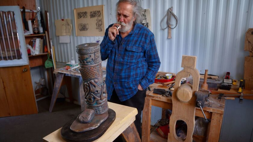At his studio in El Cajon, Alaa Al Saffar looks over a scaled model of an art piece he calls Rock Freedom that he would love to create here in San Diego.