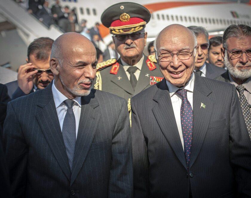 Pakistani foreign affairs advisor Sartaj Aziz, right, walks with Afghan President Ashraf Ghani during his visit to Islamabad, Pakistan, on Friday.