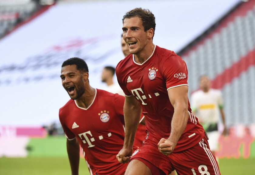 Bayern's Leon Goretzka, right, celebrates with Serge Gnabry after he scores his side second goal during the German Bundesliga soccer match between Bayern Munich and Borussia Moenchengladbach in Munich, Germany, Saturday, June 13, 2020. Because of the coronavirus outbreak all soccer matches of the German Bundesliga take place without spectators. (Matthias Balk/Pool via AP)