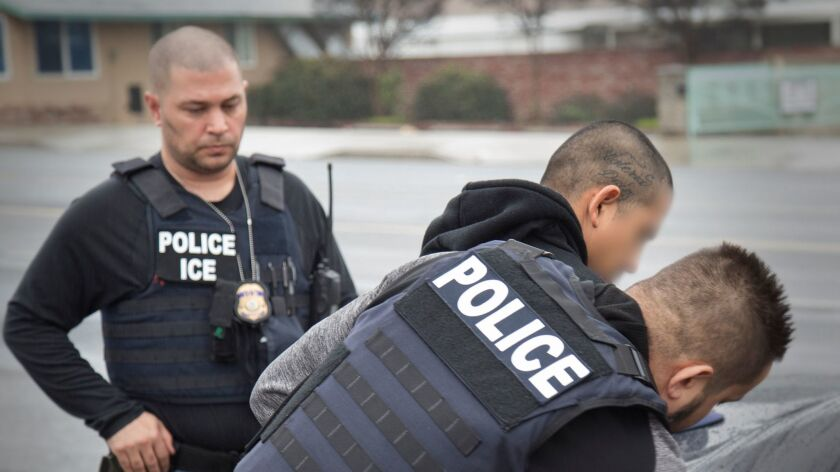 Immigration agents showing dual identification as police and ICE.