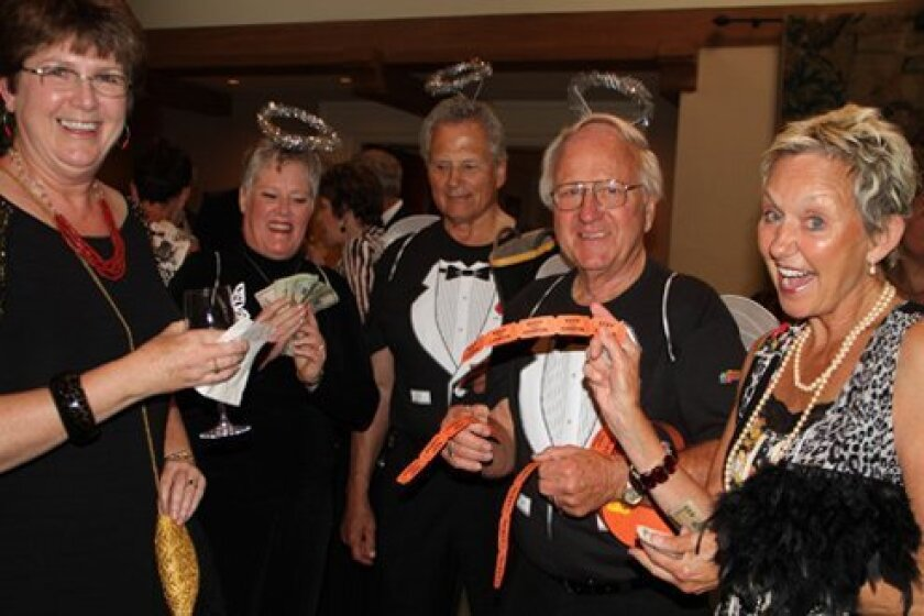 Tricia Daly (at right) a burn victim herself, made a donation to send one injured girl to a therapeutic retreat. Pictured with Daly are La Jolla Sunrise Rotary members selling raffle tickets in halos: Jane Wolgemuth, Bill O'Brien and Dave Duea. Guest Judy Bramer is at left. Courtesy Photo