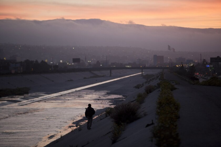 A migrant walks down the concrete channel of the Tijuana River.