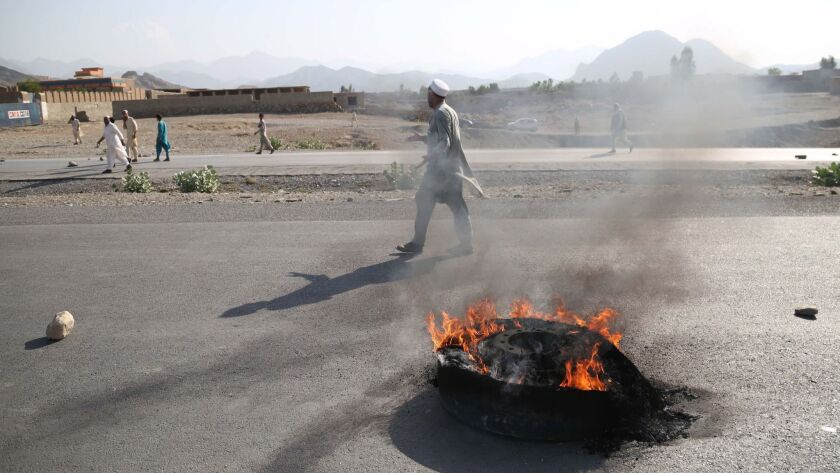 People walk near a burning tire after a suicide bomb attack in the Momandara district of Nangarhar province, Afghanistan, on Sept. 11.