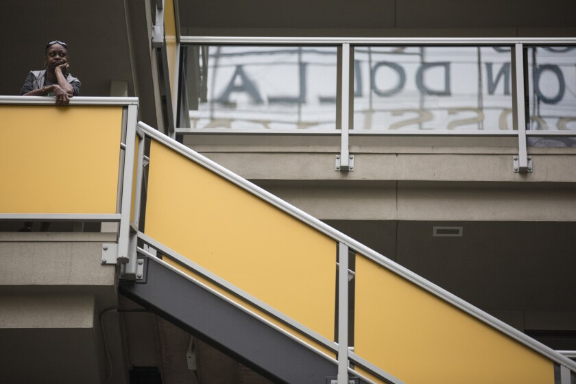 A resident watches a press conference for Prop HHH from a balcony at the downtown New Genesis Apartments last month.