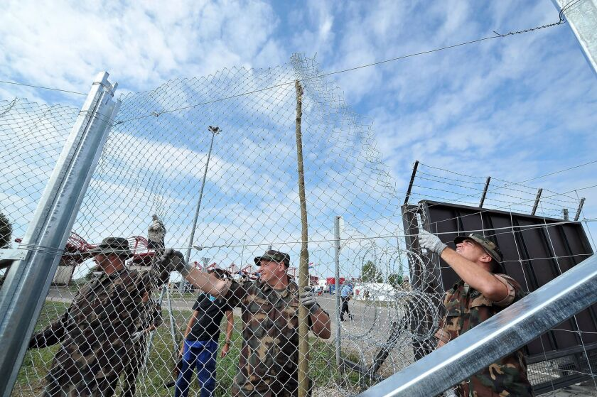 Hungarian soldiers raise fences at the Croatian-Hungarian border crossing between the villages of Baranjsko Petrovo Selo, Croatia, and Beremend, Hungary, on Sept. 22.