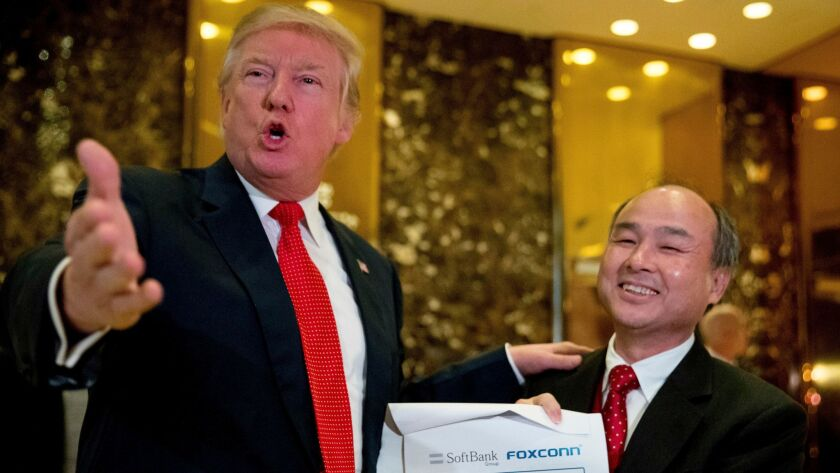 President-elect Donald Trump, accompanied by SoftBank CEO Masayoshi Son, speaks at Trump Tower in New York.