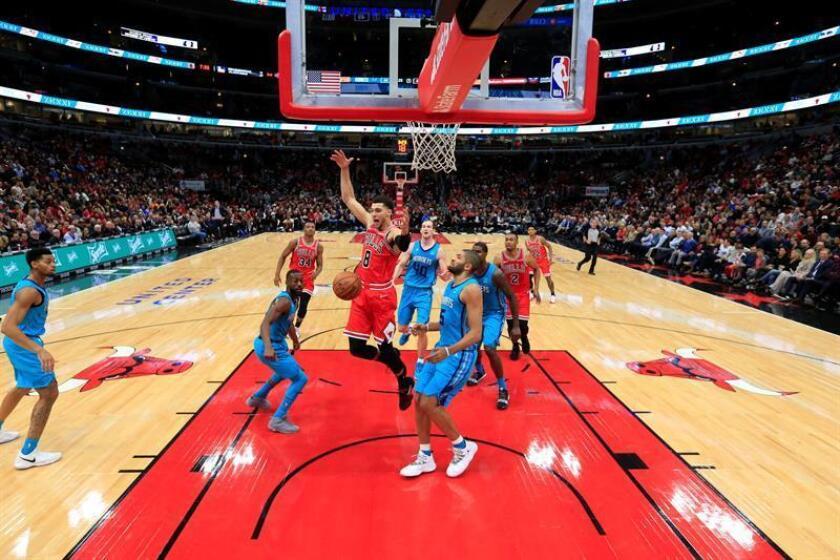 Zach LaVine (c) de Bulls pierde el balón junto al francés Nicolas Batum (d) de Charlotte Hornets en un juego de la NBA entre Charlotte Hornets y Chicago Bulls en United Center en Chicago (EE.UU.). EFE