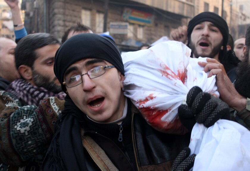 Mourners carry the body of a comrade killed during Syrian rebel battles in the northern city of Aleppo, on Jan. 8, 2014.
