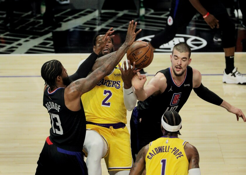 The Lakers' Andre Drummond can't grab a rebound while being double-teamed by the Clippers' Paul George and Ivica Zubac.