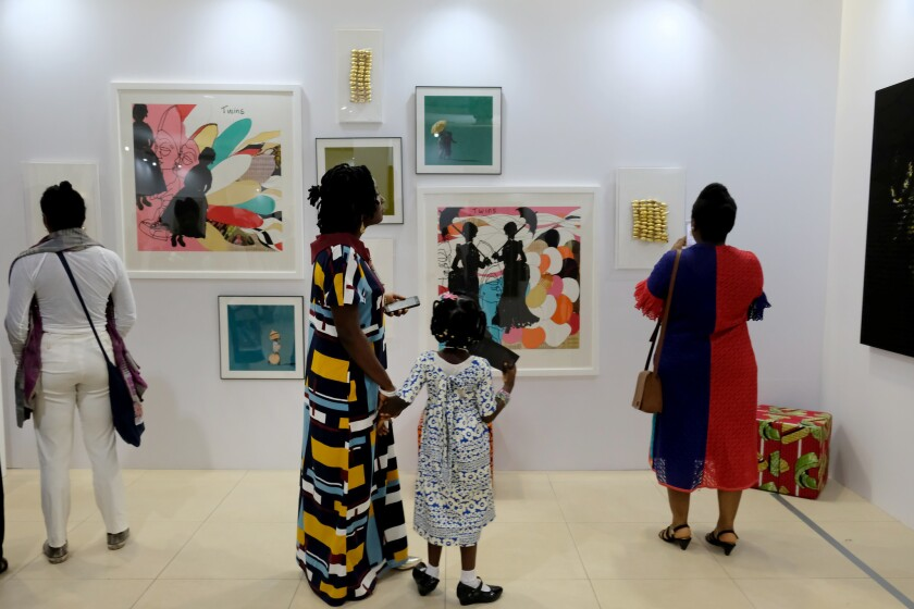 Visitors look at works on display at Art X Lagos, an international art fair that took over the Lagos Civic Center in November 2017.