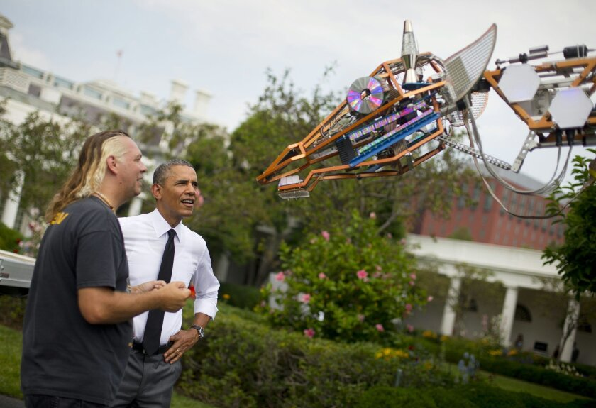 President Barack Obama meets Lindsay Lawlor of San Diego and his creation, a 17-foot-tall, 2,200-lb robotic giraffe during the first White House Maker Faire on Wednesday. (AP Photo/Pablo Martinez Monsivais)