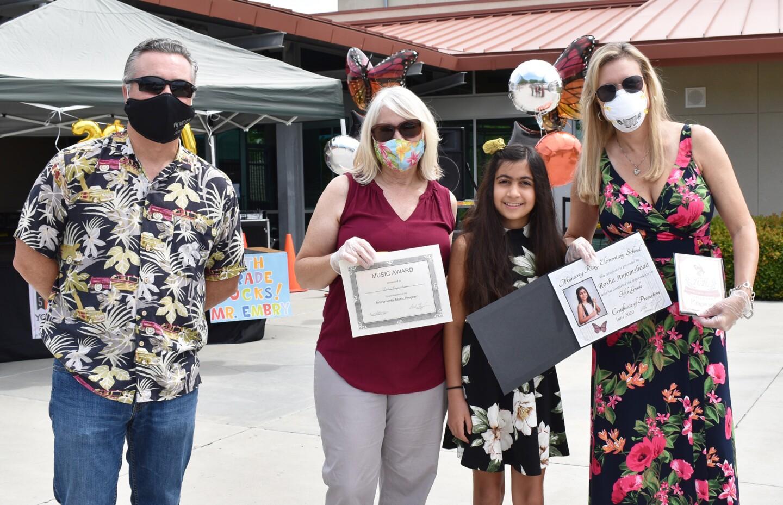 Principal Sal Embry, school aide Nicole Moore, fifth grader Rosha Anjomshoaa and fifth grade teacher Dianne Decker.