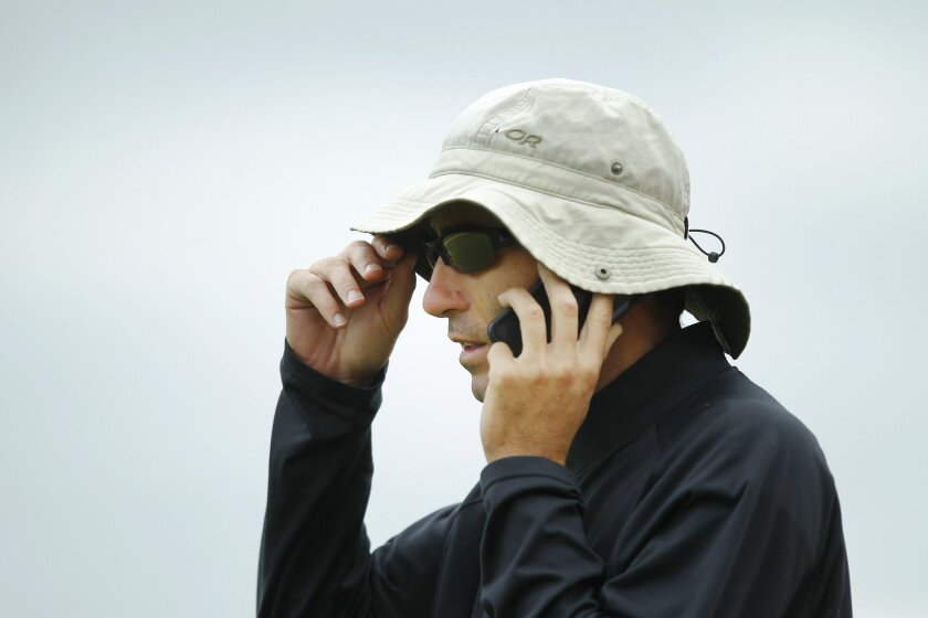 San Diego Padres A.J. Preller talks on the phone during a spring training practice.