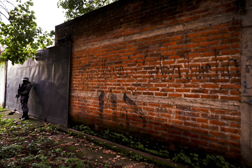 A police officer stands guard next to a graffiti wall with the name of a gang as part of a routine patrol in Lourdes, La Libertad, El Salvador, on Oct. 10, 2019. Human Rights Watch said that at least 138 people deported to El Salvador from the U.S. in recent years were subsequently killed. The new report comes as the Trump administration makes it harder for Central Americans to seek refuge here.