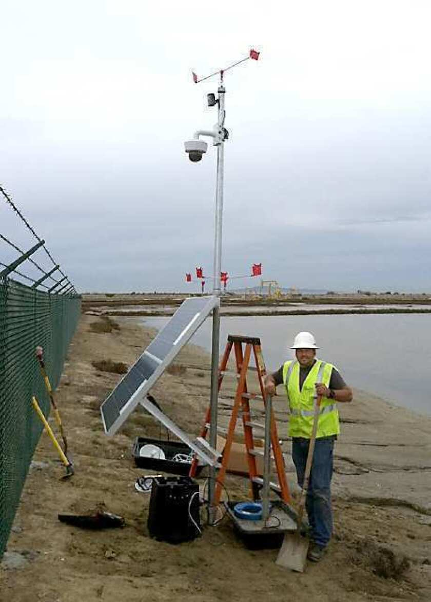 Brian Pavloff, president of Variable Speed Solutions, finishes the installation of web camera in the Bolsa Chica Ecological Reserve. It will be recording the activities of the Western Snowy Plover and the California Least Tern.