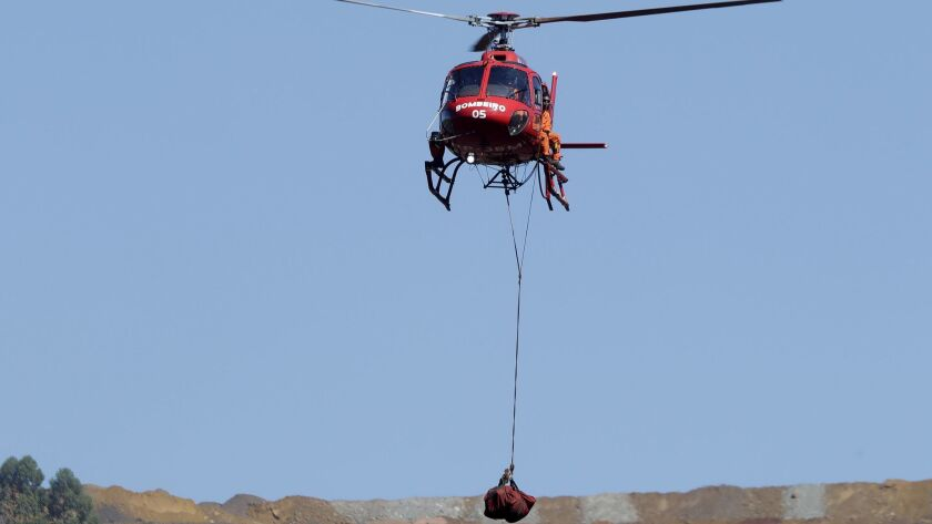 A helicopter lifts a body recovered from the mud days after a mining company's dam collapsed in Brum