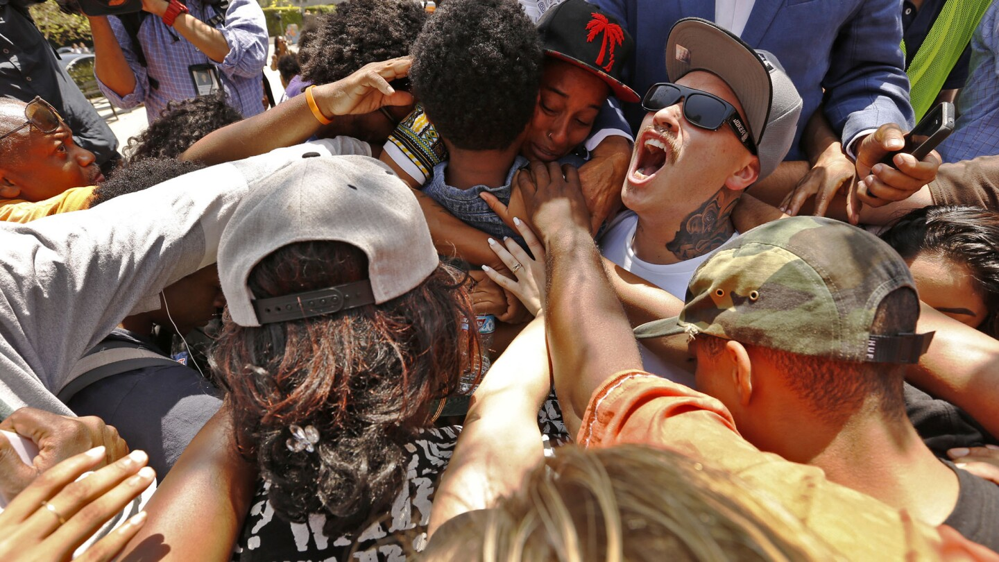 Jasmine Abdullah, top center, is surrounded by the chanting crowd outside the Los Angeles Police Department headquarters Tuesday.